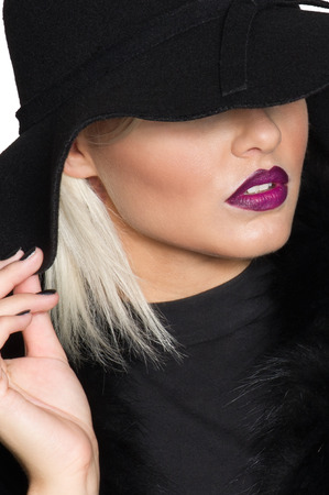 High angle view of a gorgeous sensuous chic blond woman in a wide brimmed black hat concealing her eyes but revealing her parted red lips