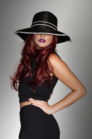 Elegante vrouw in een stijlvolle zwarte outfit en bijpassende zwarte hoed verleidelijk voor haar ogen poseren zijwaarts met haar handen op haar heupen te draaien om te kijken naar de camera