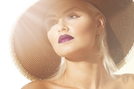 Close up head shot of a gorgeous sophisticated exotic young blond woman wearing a wide brimmed hat facing into sun flare Stock Photo