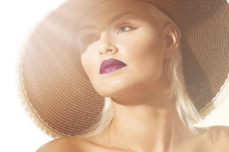 Close-up hoofd geschoten van een prachtige verfijnde exotische jonge blonde vrouw draagt een hoed met brede rand uitkijkend op zongloed