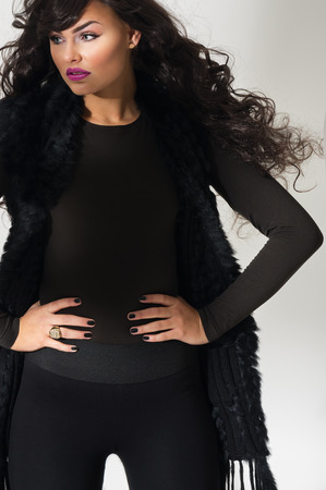 Confident attractive young fashion model with flowing long curly auburn hair standing with her hands on her hips in an elegant black ensemble, close up view over grey