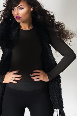 Zekere aantrekkelijke jonge mode-model met stromend lang krullend kastanjebruin haar staande met haar handen op haar heupen in een elegant zwart ensemble, close up uitzicht over grijs