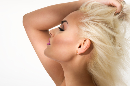 Graceful gorgeous blond woman standing with her arm raised above her head with her eyes closed and a blissful serene expression, close up profile view head shot over white