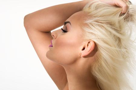 visage profil: Graceful superbe femme blonde debout avec son bras levé au-dessus de sa tête avec ses yeux fermés et une expression sereine heureux, close up vue de profil, tête, coup sur blanc