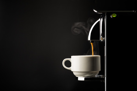 Preparing a cup of strong freshly brewed espresso coffee using a coffee machine with a side view of the beverage pouring into a white cup on a dark shadowy background
