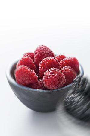 Bowl of fresh juicy raspberries against white background