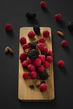 Bunch of raspberries with blackberries scattered against wooden cutting board