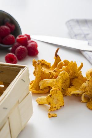 Verse hanenkam champignons van een herfst bos op een keukentafel naast rijpe rasp bessen klaar om te worden gebruikt in de keuken Stockfoto