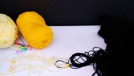 yellow,white and black yarn balls for crochet with accessories on wooden table. close up shot Standard-Bild