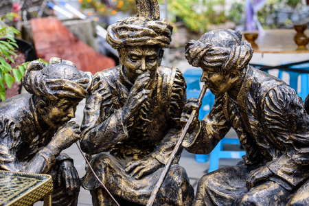 Bronze statue of villagers smoking from a pipe