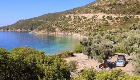 Camping car with elevating roof and clotheslines between olive trees, close to the ocean with turquoise water near Pilion, Greece.