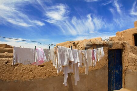 Clotheslines with white laundry on a brown loam house, under the blue sky of Marakech, Morocco.