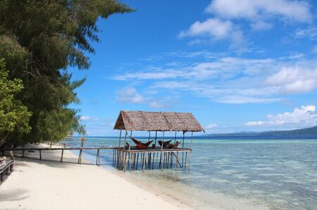 Stilt platform with hammocks over the water on a tropical beach in Raja Ampat on a sunny day.