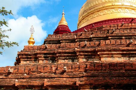 Brick pagoda with red and golden spurs in Bagan, Myanmar  Burma. Stock Photo