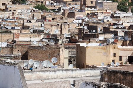 Skyline of the poor city Fès with brown houses and satellite dishes.