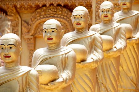 Golden Statues with red lipstick in a row in front of the Golden Temple in Phnom Penh, Cambodia, south-east Asia. Imagens