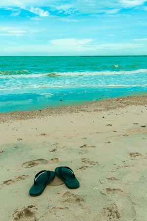 Black Slippers on the beach with blue sky photo