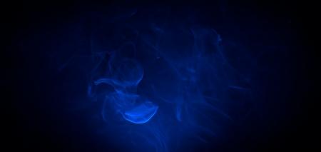 Blauwe rook in het donker op een zwarte achtergrond