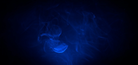 Blue smoke in the dark on black background photo