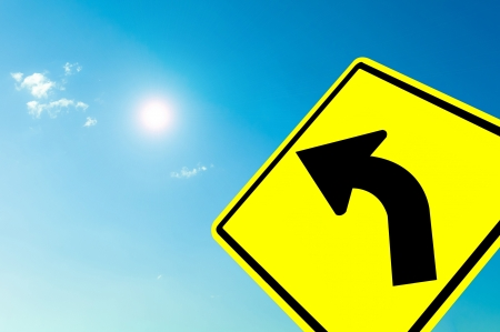 Curved road Traffic Sign on blue sky cloudy and sun photo