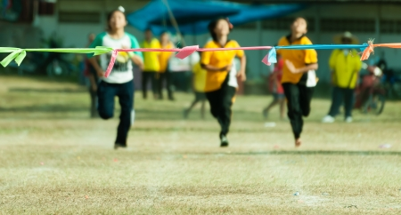 Three child girl sprinting  to finish line in sport day of school in thailand