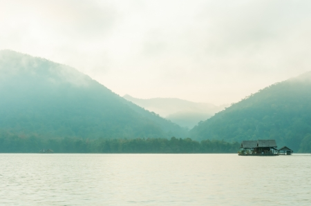 Hut on water in morning time with mountain and fog photo