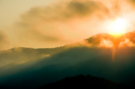 Sunrise on mountain with misty fog early in morning time photo