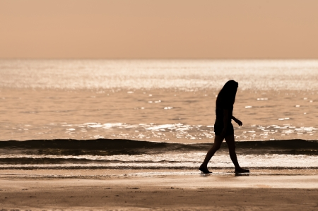 limitless: sillhouette woman walking on the beach