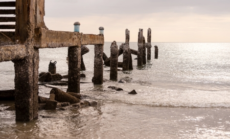 Old jetty in sea in overcast sky day evenning time photo