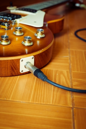 Electric guitar honey burst color on floor with jack cable photo