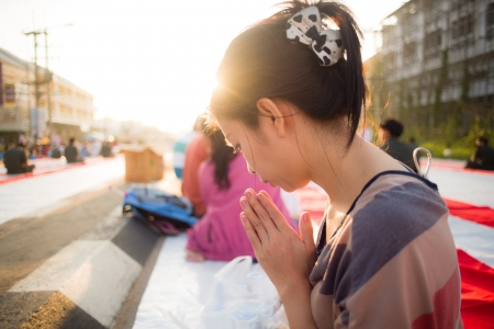 Asian girl put the palms of the hands together in salute with sun light photo