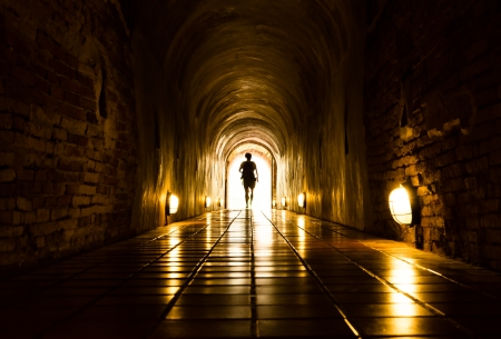hallway: silhouette of human in old brick tunnel light at end of tunnel