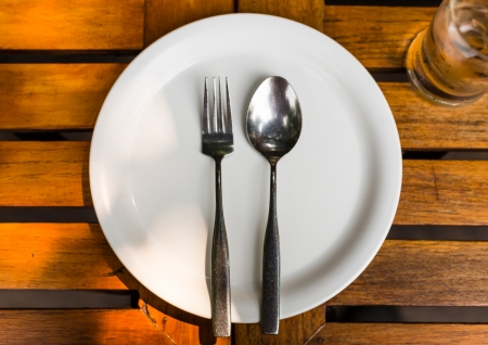 Fork and Spoon on white dish on wood table