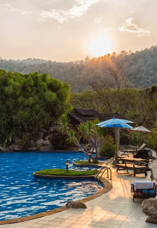 Outdoor Swimming Pool with sunset behind mountain