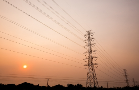 silhouette of power transmission towers with sunset in background photo