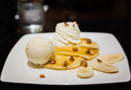 vanilla ice cream on pancake banana split on white dish photo
