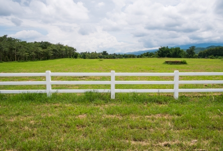 white fence in farm field and overcast sky