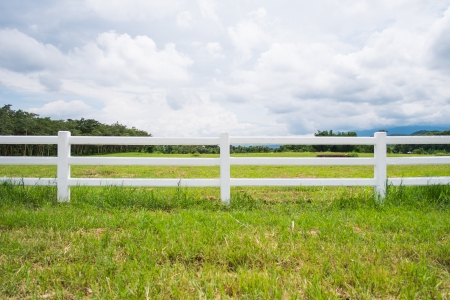 pasture fence: white fence in farm field and overcast sky