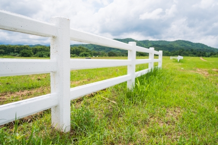 white fence in farm field and overcast sky photo