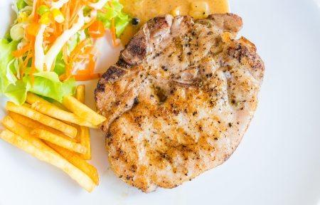 T-bone pork steak on white dish with salad french fries and pepper gravy sauce