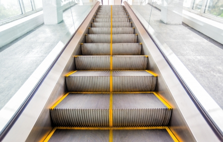 perspective escalators stairway with yellow line photo