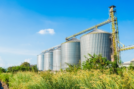 Industrial factory of animal feed storage with blue sky background in thailand photo