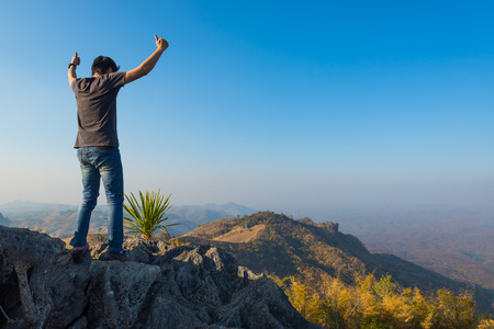 man standing on stone top of high mountain