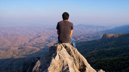 man zittend op steen boven op een hoge berg
