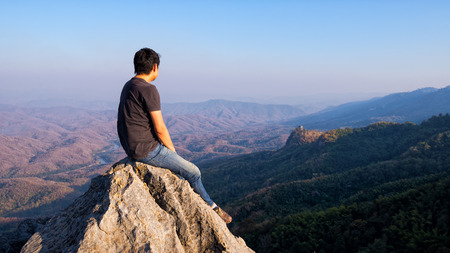 man sitting on stone top of high mountain photo