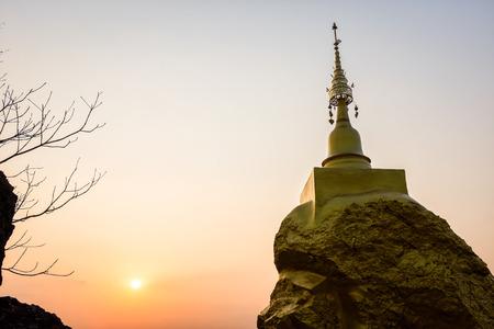 gouden pagode op gouden rots steen op berg met zonsondergang op de achtergrond Stockfoto