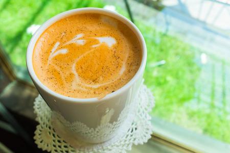 Matcha groene thee in witte kop met melkschuim tekenen op de top