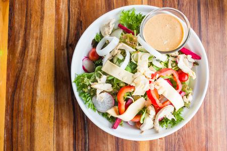 kip kaas en groenten salade met caesar dressing saus in witte schotel op houten tafel in het restaurant