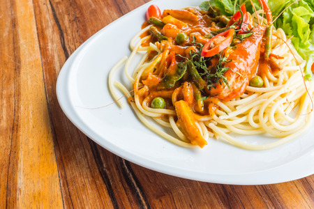 spaghetti met garnalen Panag pittige Thaise saus groenten en Thaise kruid op witte schotel op houten tafel in het restaurant
