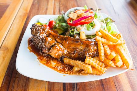 biefstuk barbecue varkensvlees spareribs met saus sesam op topping groenten en frieten op witte schotel op houten tafel in het restaurant